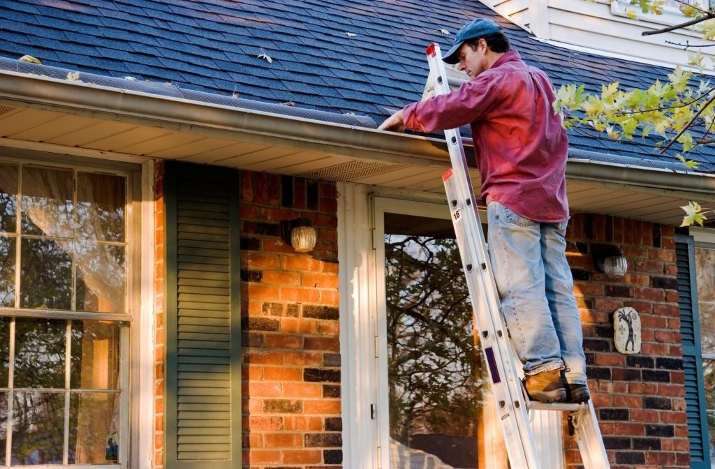 Man standing 5 feet up a ladder leaning against a house roof looking while he looks into a gutter on an autumn day