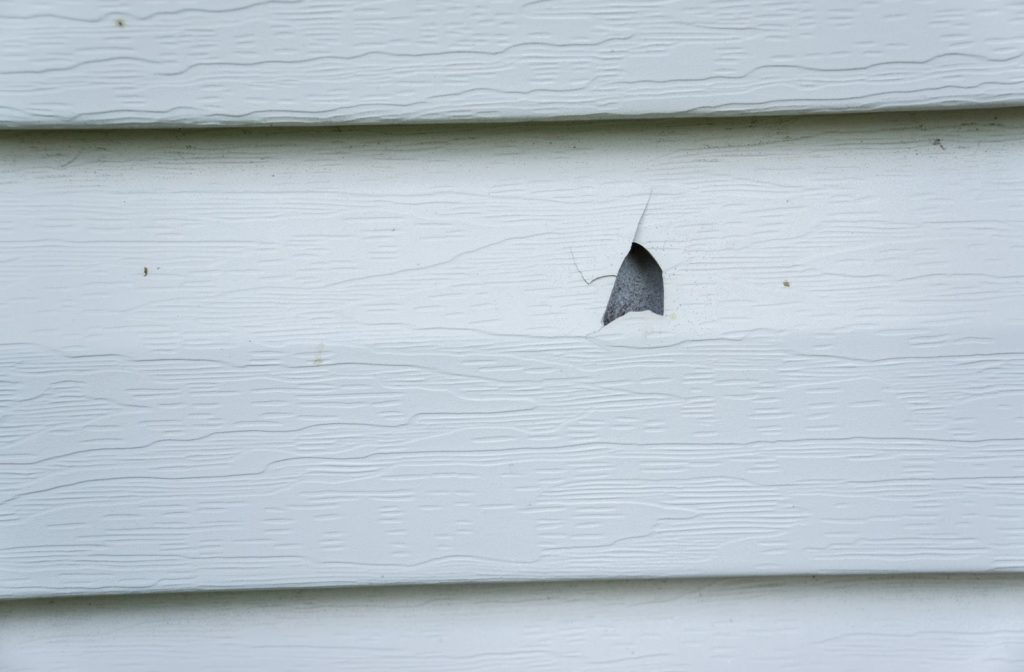 Vinyl siding which has been damaged after a hail storm