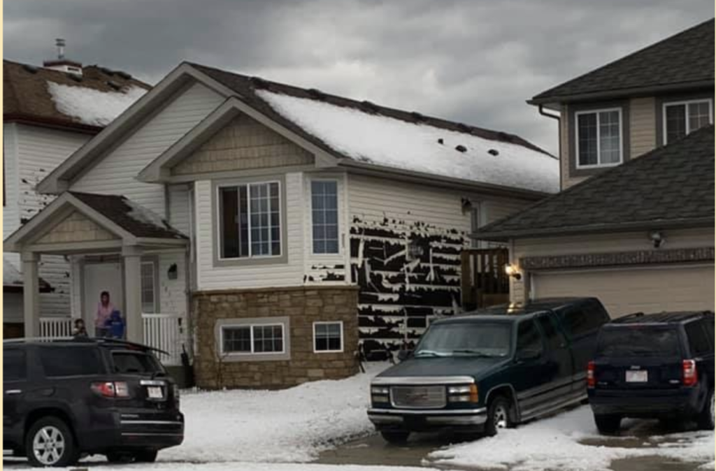 Hail damage caused to the siding of house during Calgary storm.