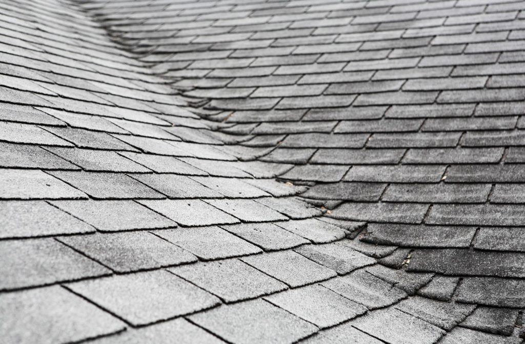 The corner of a roof covered in old, run down shingles