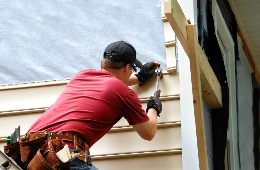 Young professional installing house siding