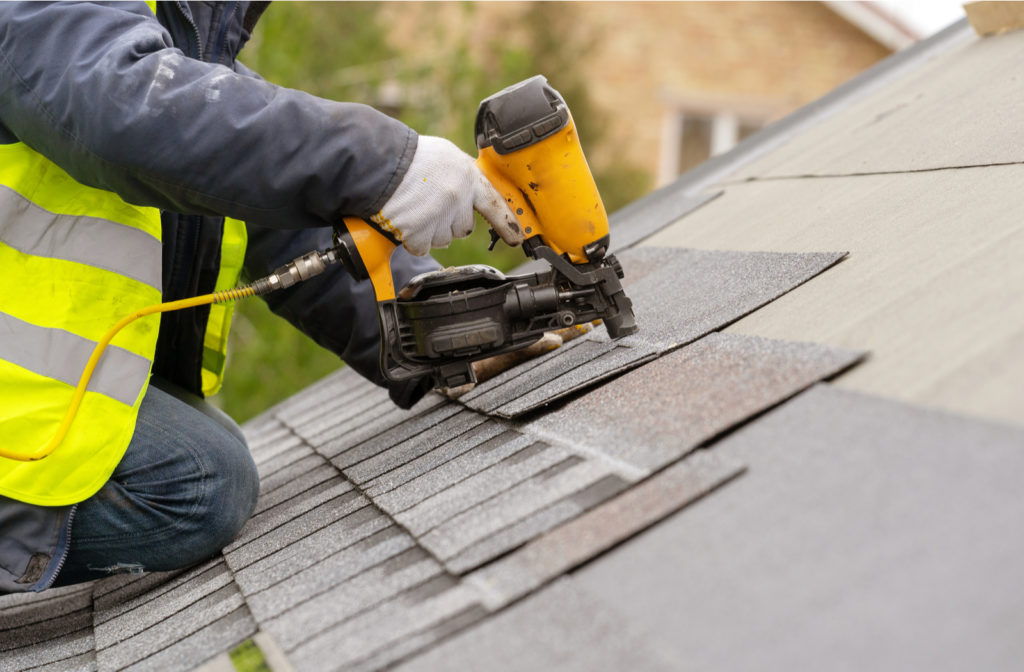 Professional with safety vest, gloves and pneumatic nail gun installing new roof on house